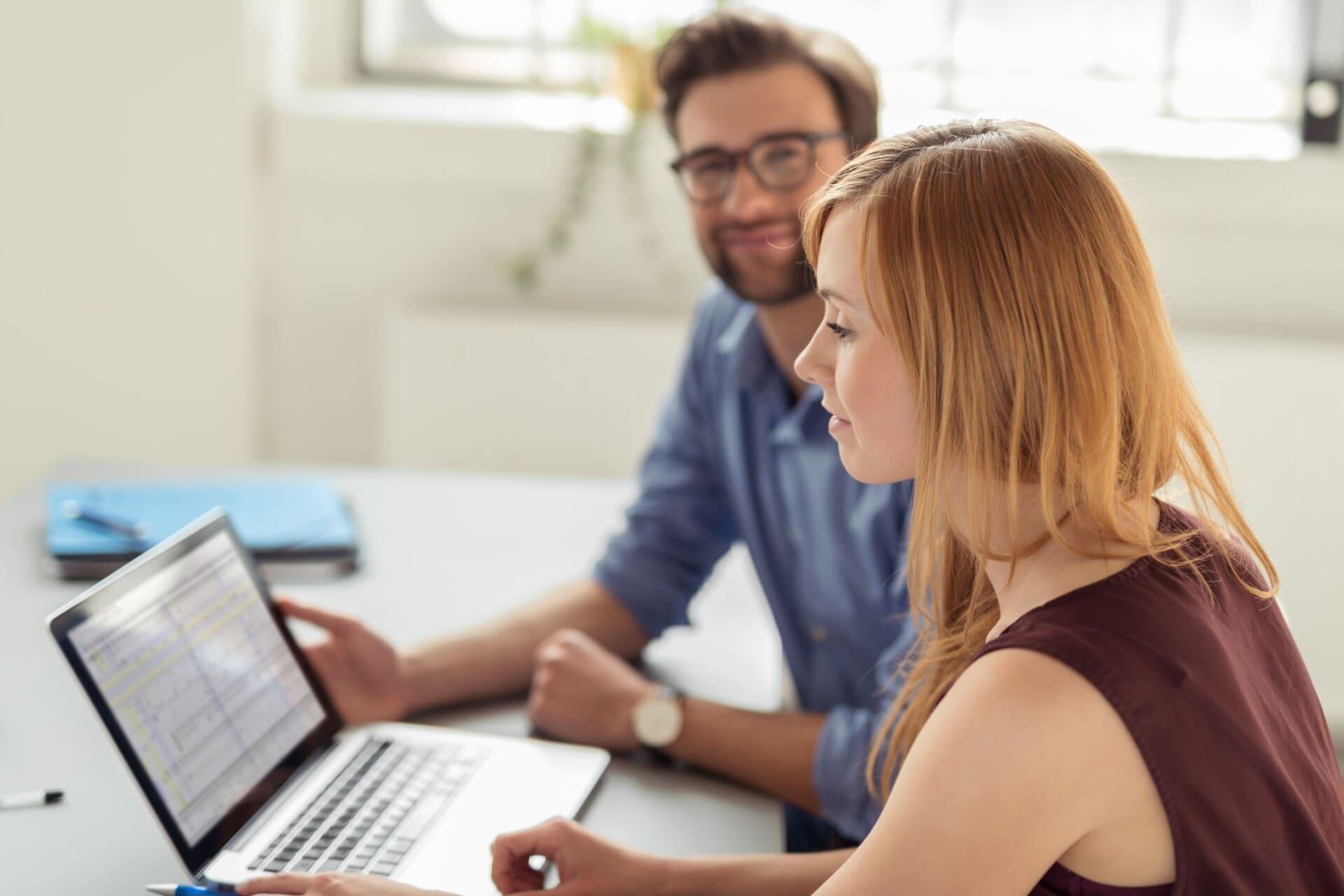 man en vrouw bij pc aan een bureau