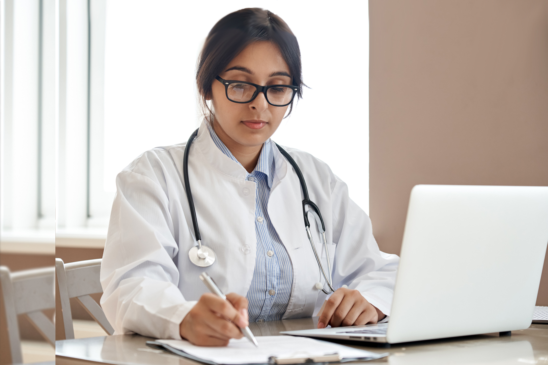 Indian ethnic female doctor physician gp wearing glasses white coat stethoscope writing filling medical form watching online medical webinar seminar training working sitting with laptop at workplace