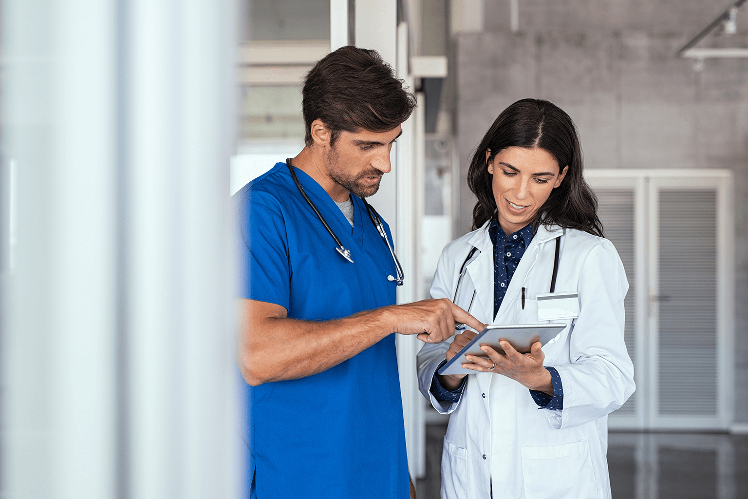 female-doctor-male-nurse-reviewing-information-on-tablet-in-hospital