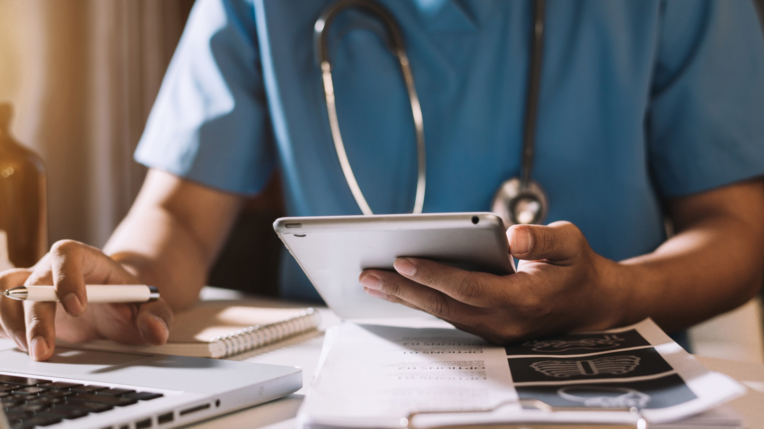 Healthcare professional working at desk on laptop and clipboard of papers with tablet and pen in each hand