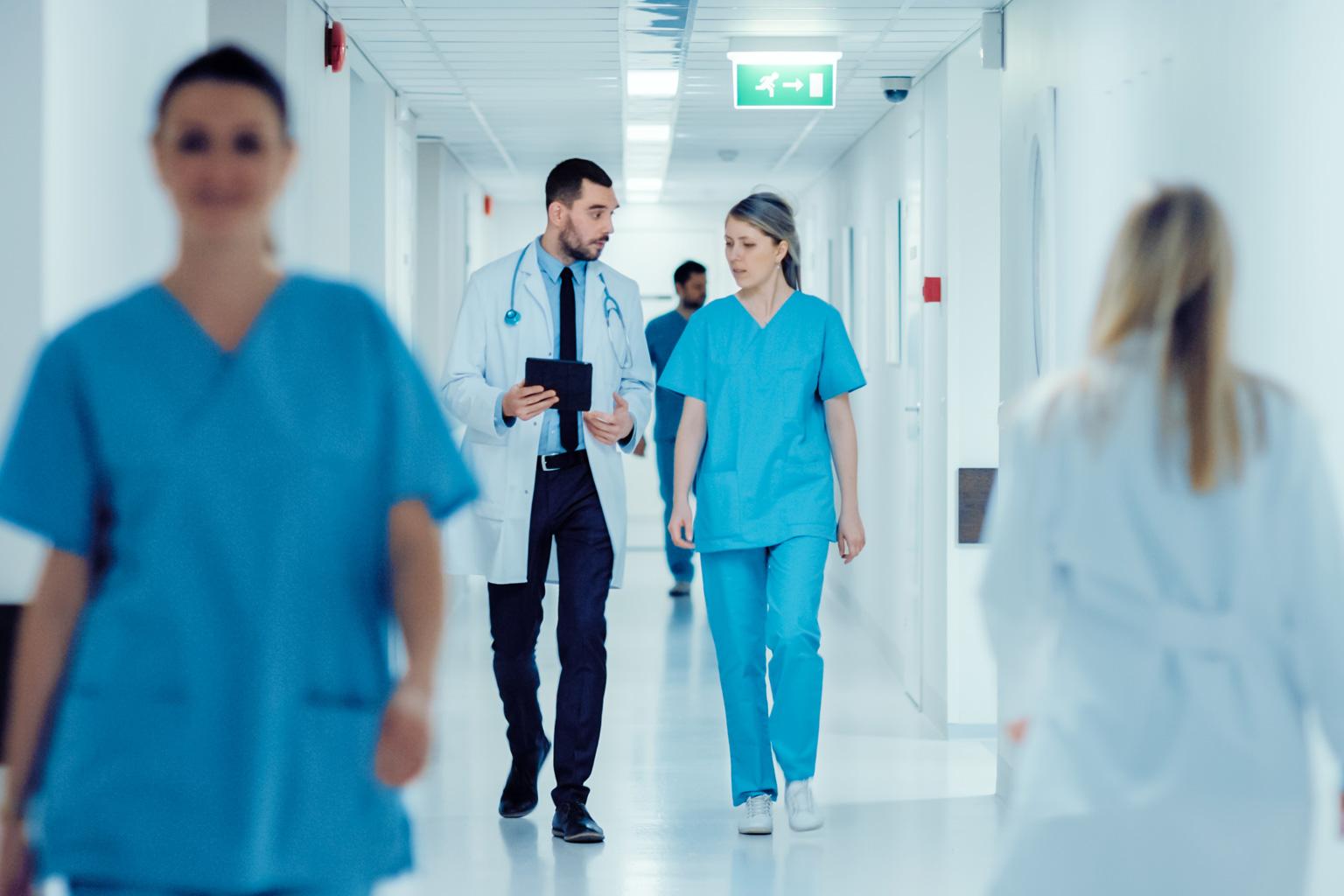 Korytarz szpitala, idący lekarze rozmawiają o Progmedica