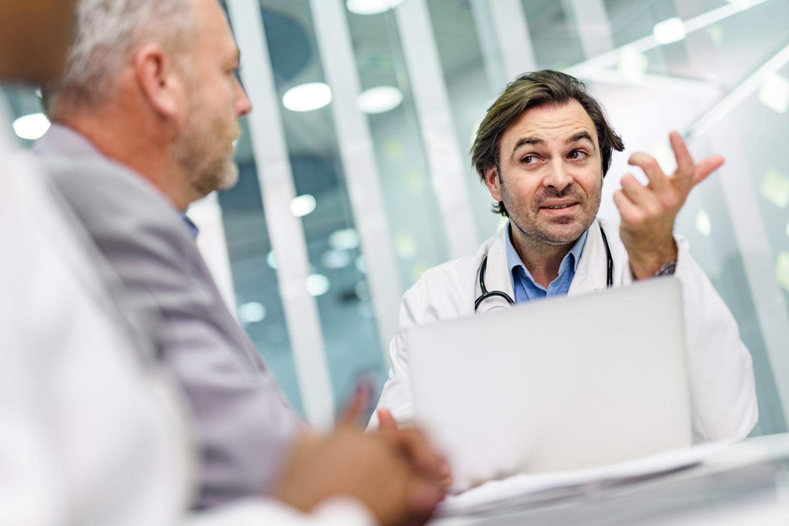Lekarz rozmawia z managerem o zdarzeniach organizacyjnych w Progmedica
