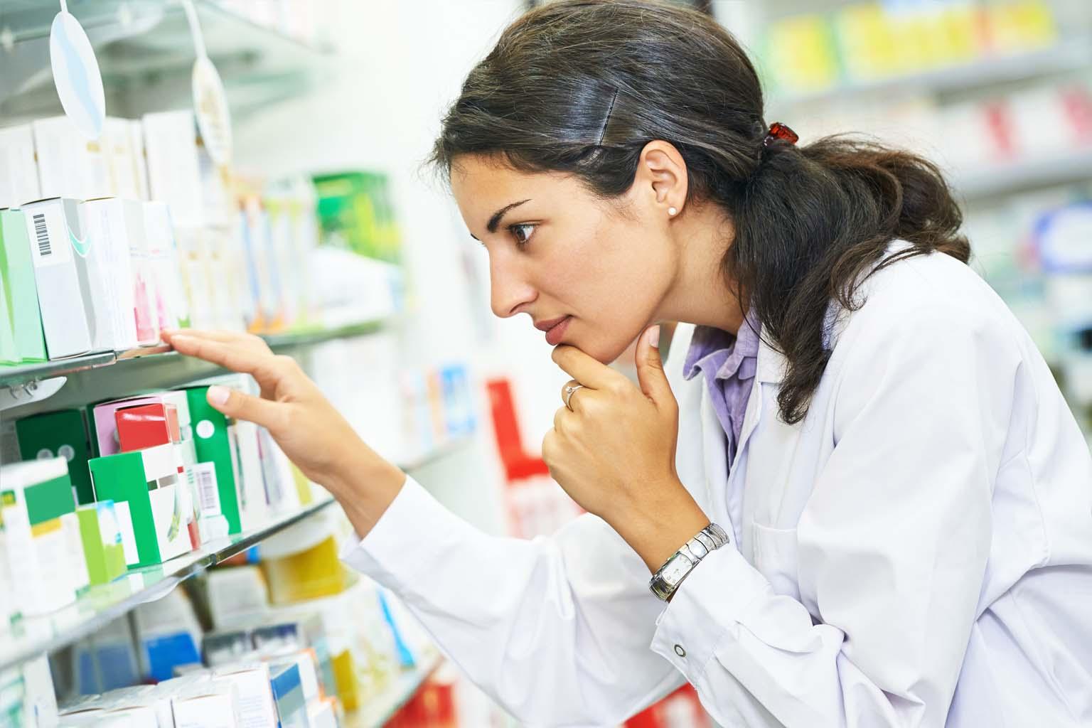 pharmacist examining medication in pharmacy