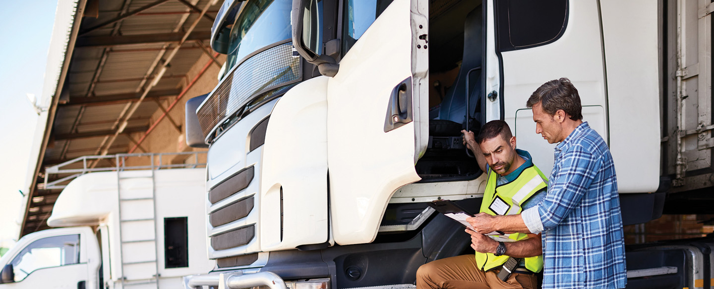 two men discussing vehicle title management of large trucks