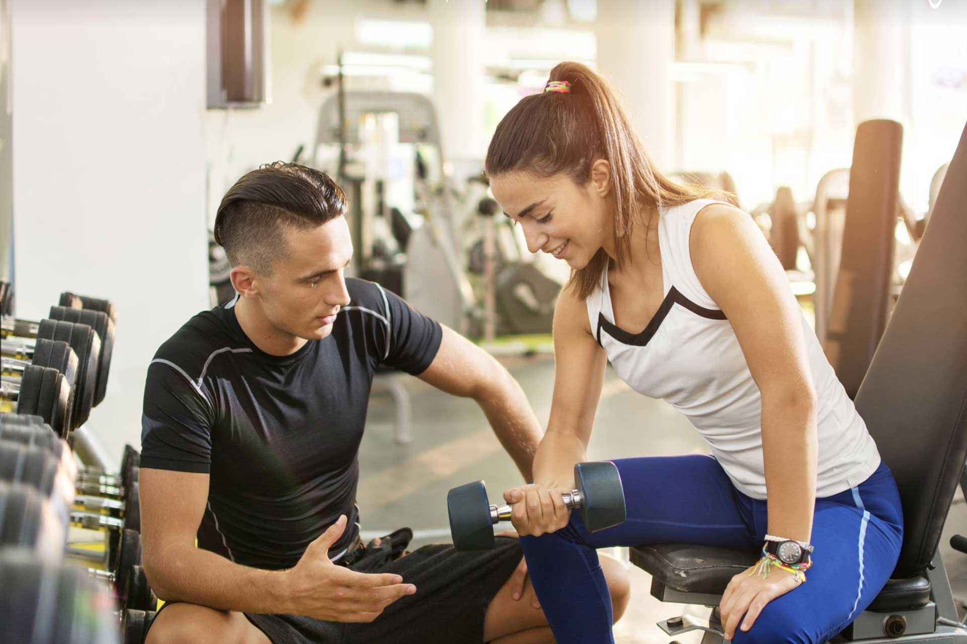 Male personal trainer working with a female client
