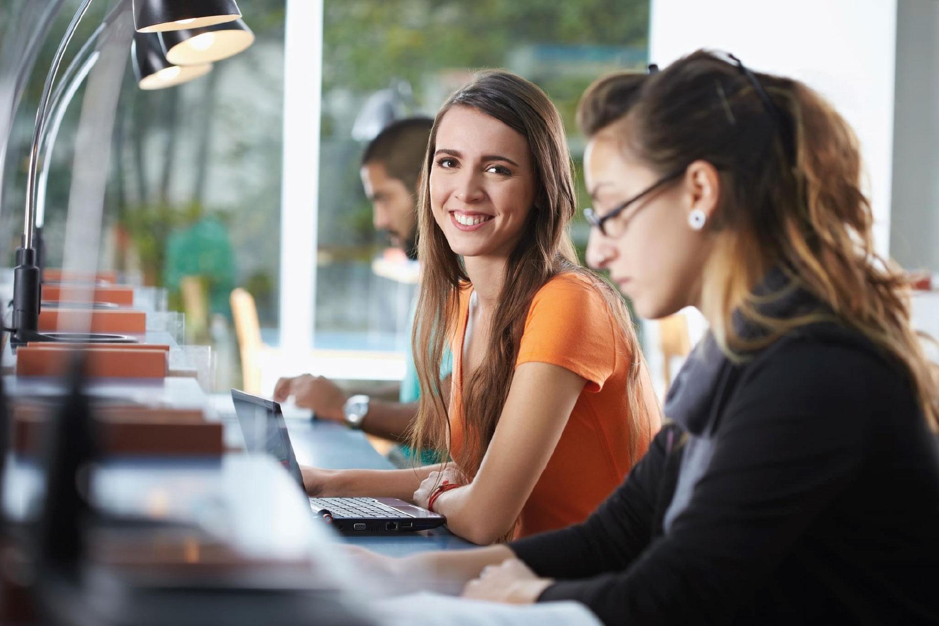 Uśmiechnięta studentka korzysta z LEX Student na laptopie
