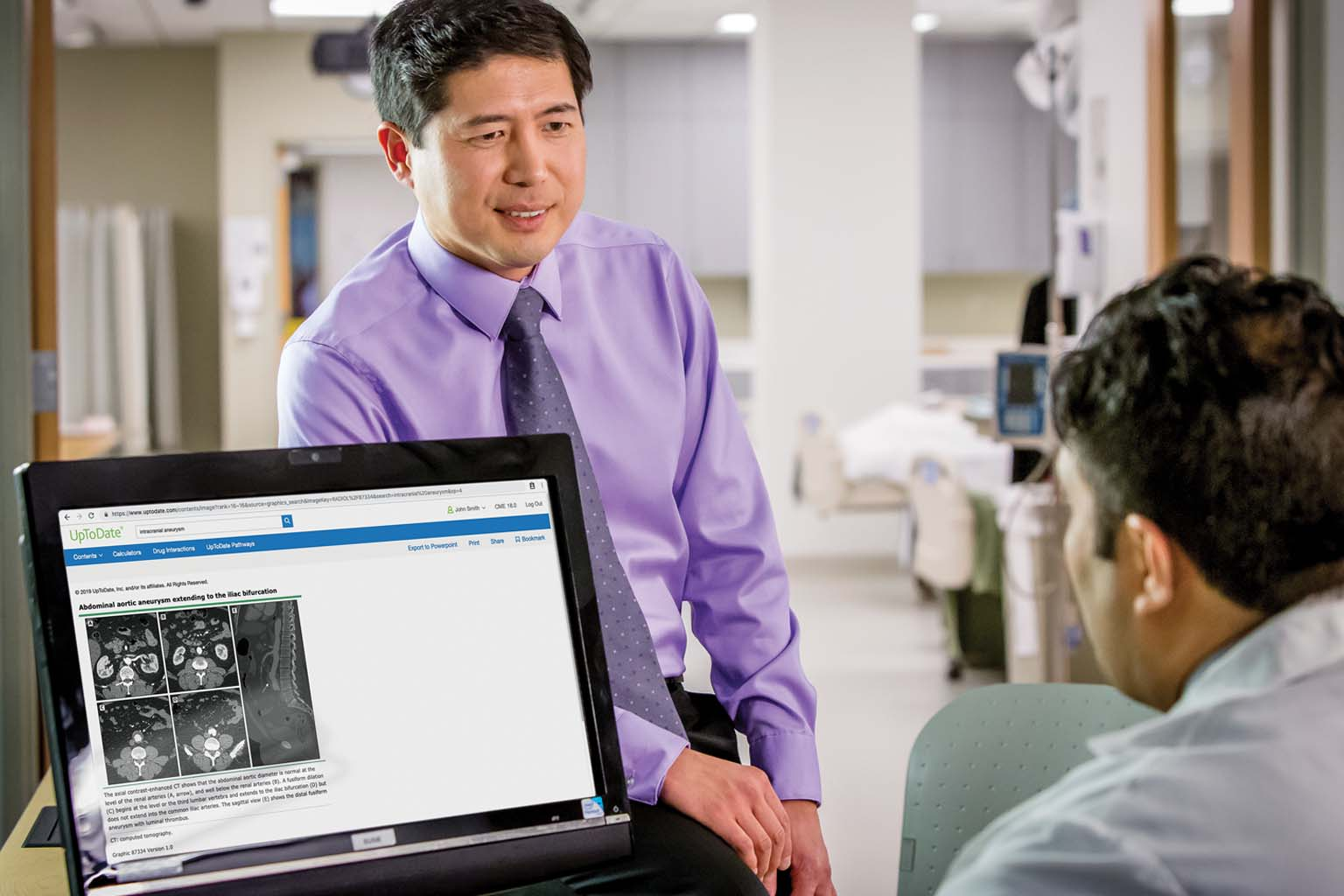 two doctors discussing information displayed on a monitor