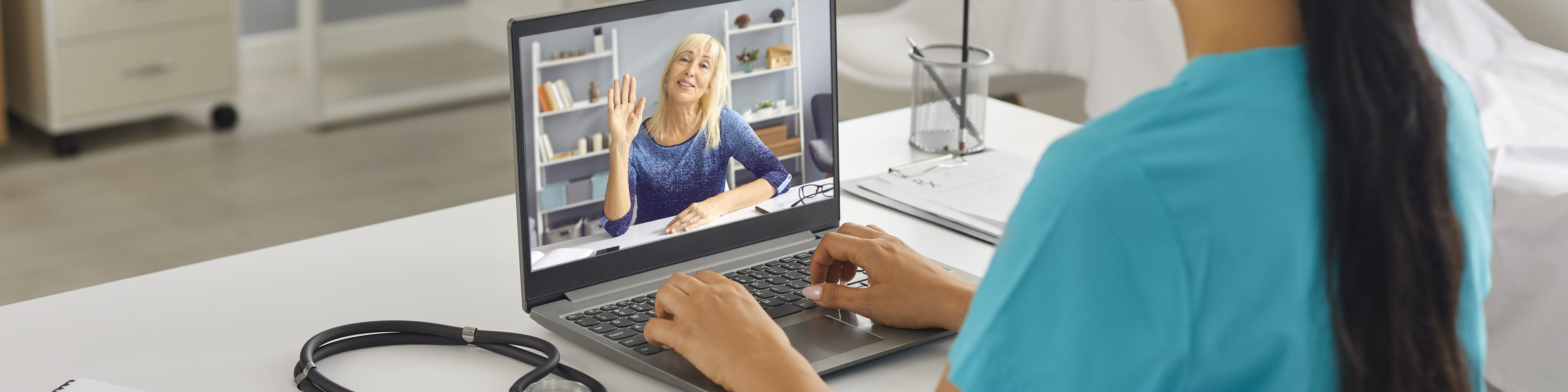 Healthcare worker sitting at desk on laptop with patient, telemedicine/telehealth