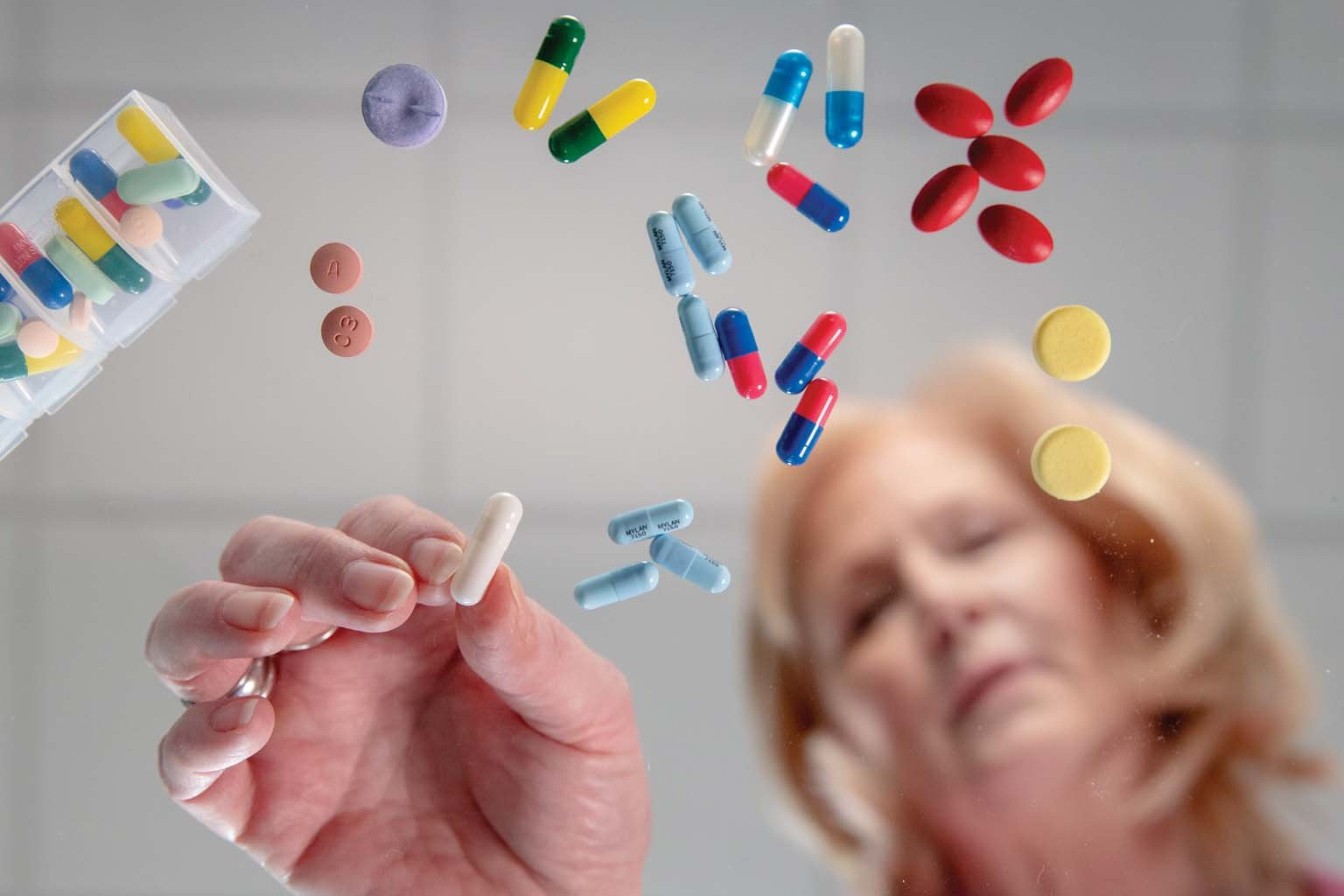 patient sorting through a variety of pills