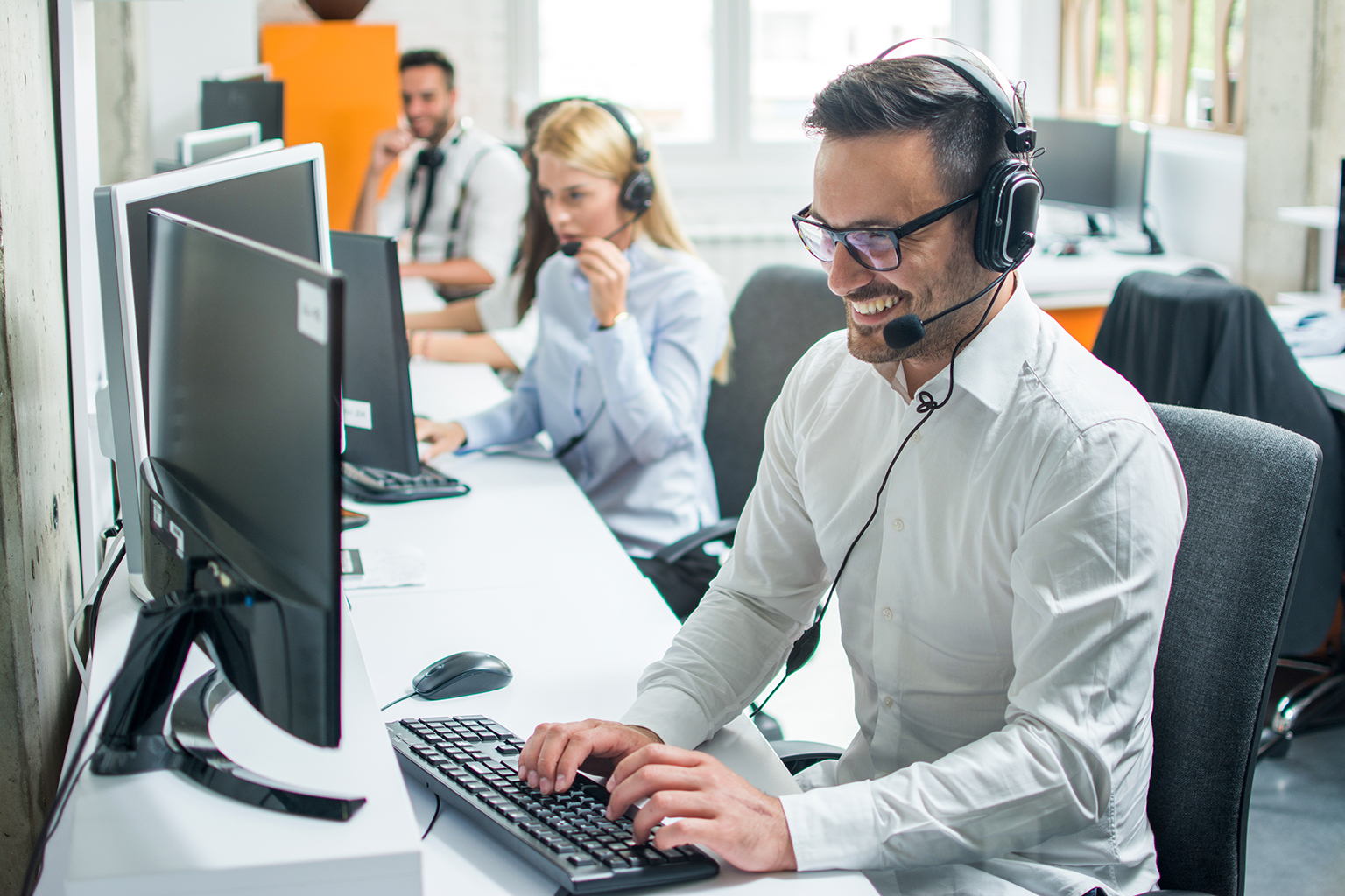 Call center staff working at computers, focus on gentleman in front on headset