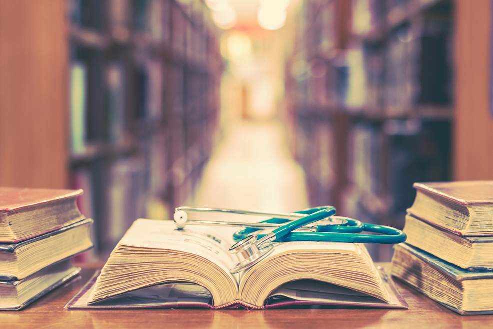 Old book in library with stethoscope on open textbook, stack piles of texts on reading desk, and aisle of bookshelves in study class room background