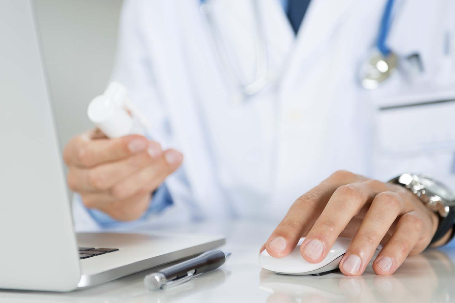 phamacist holding bottle of pills while using computer