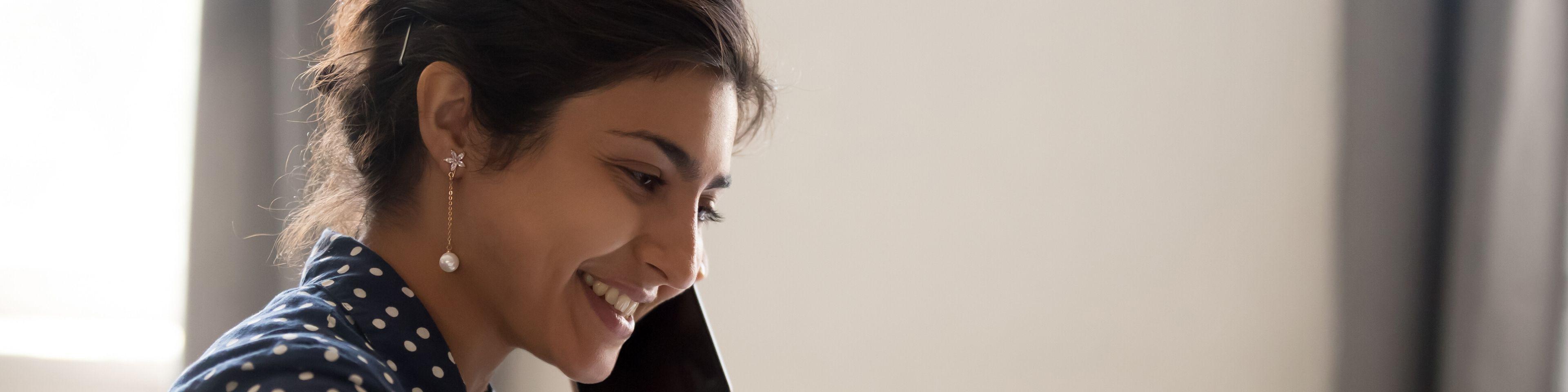 Smiling-employee-working-on-laptop-talking-over-phone