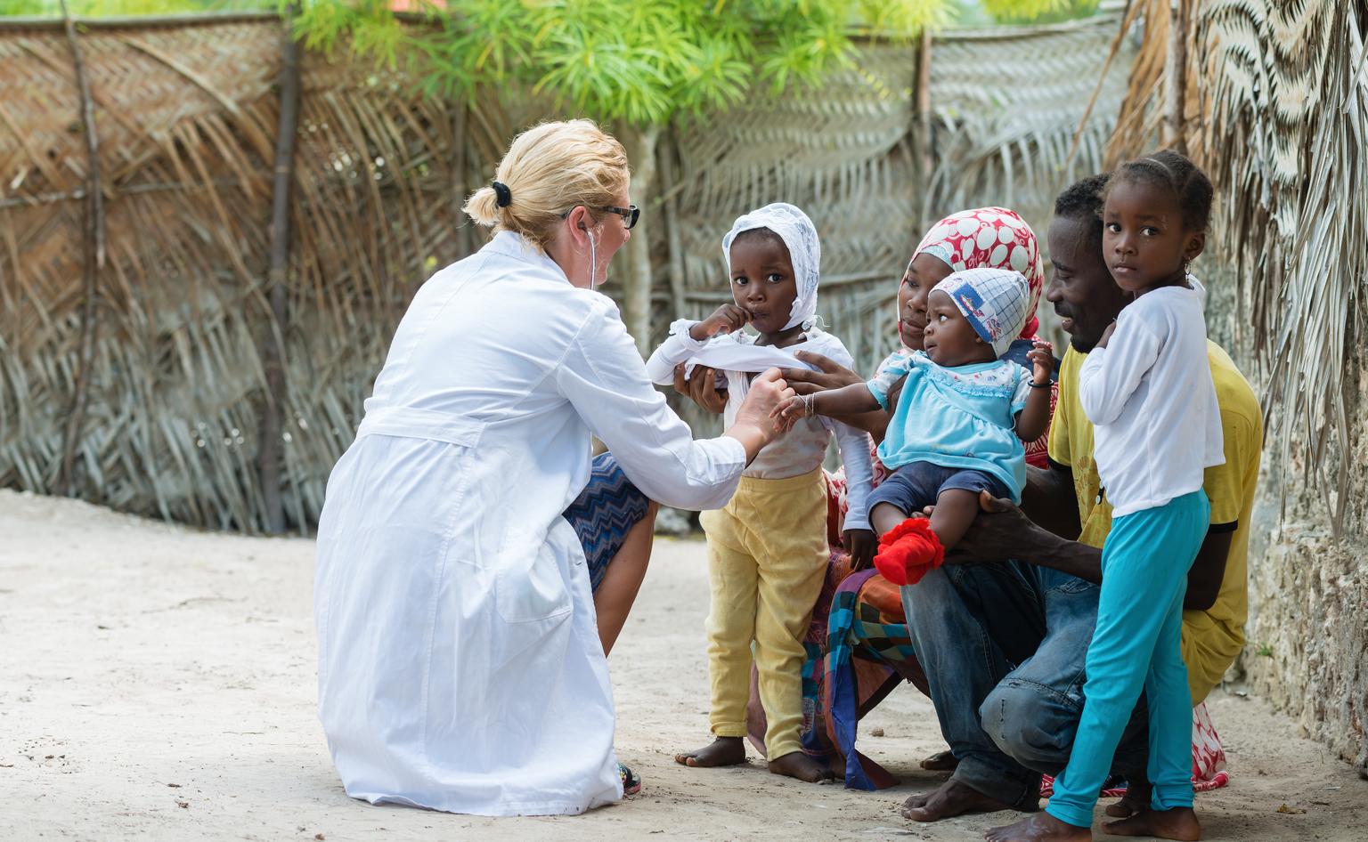 Physician listening to child's heartbeat outdoorsdoors