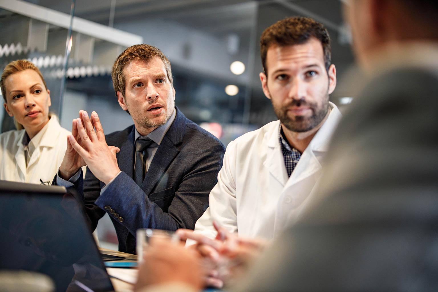 Grupa lekarzy i managerów dyskutuje w szpitalu na temat wdrożenia Progmedica