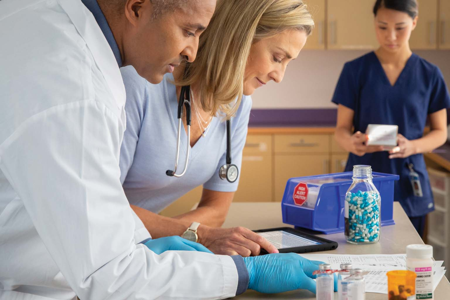 pharmacist with doctor and nurse in lab viewing tablet