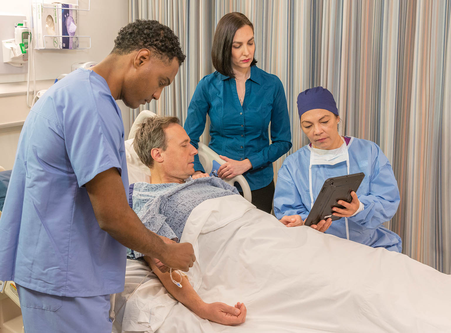 nurse and surgeon talking to male patient