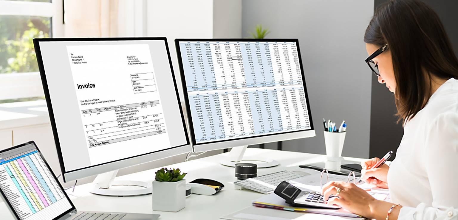 Kvinna jobbar med revision på tre skärmar