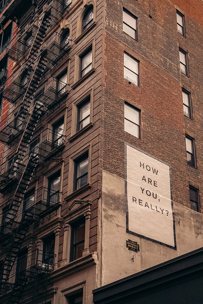 A high rise residential build with a sign on the side: How are you, really?