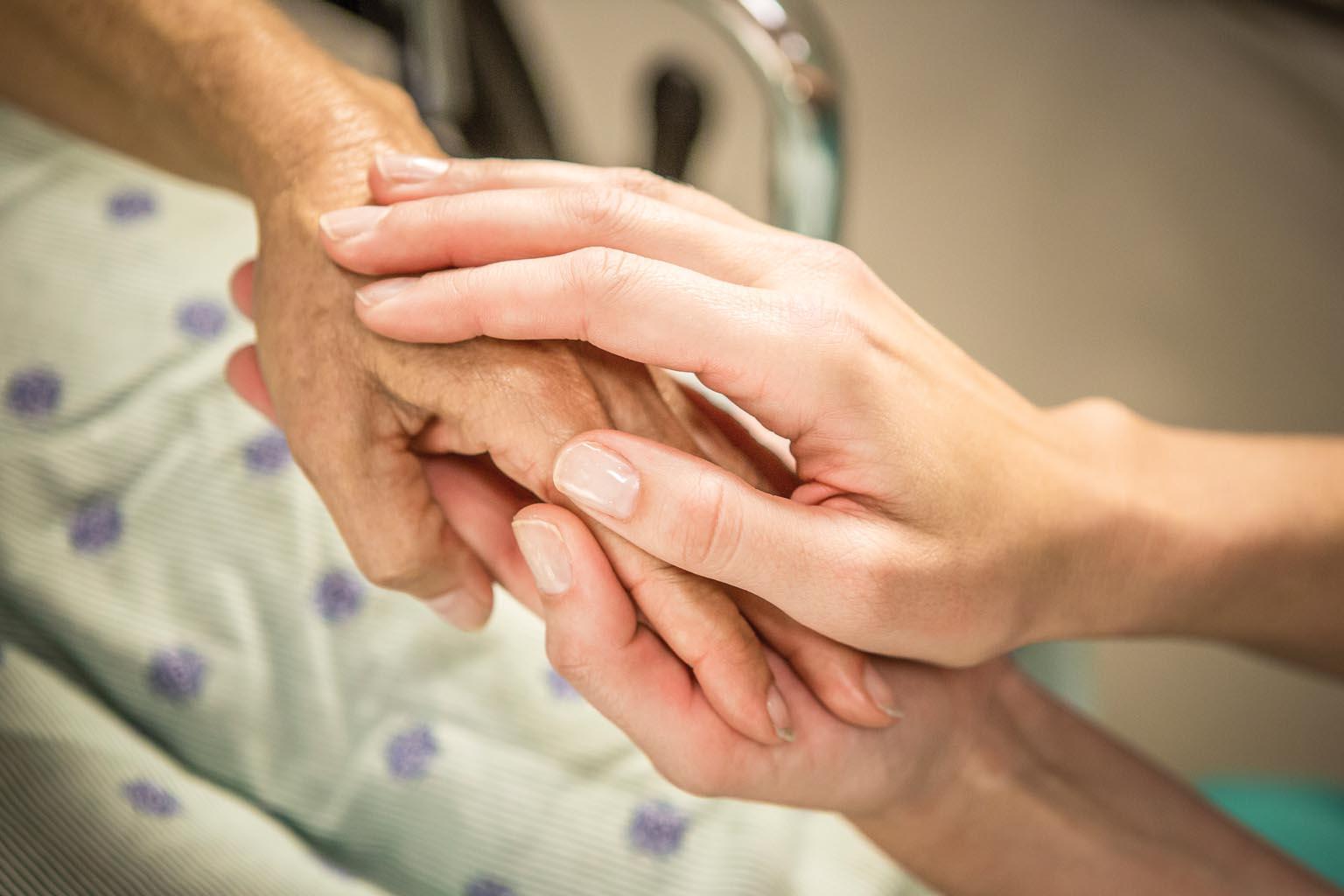 closeup of caregiver holding patient's hands