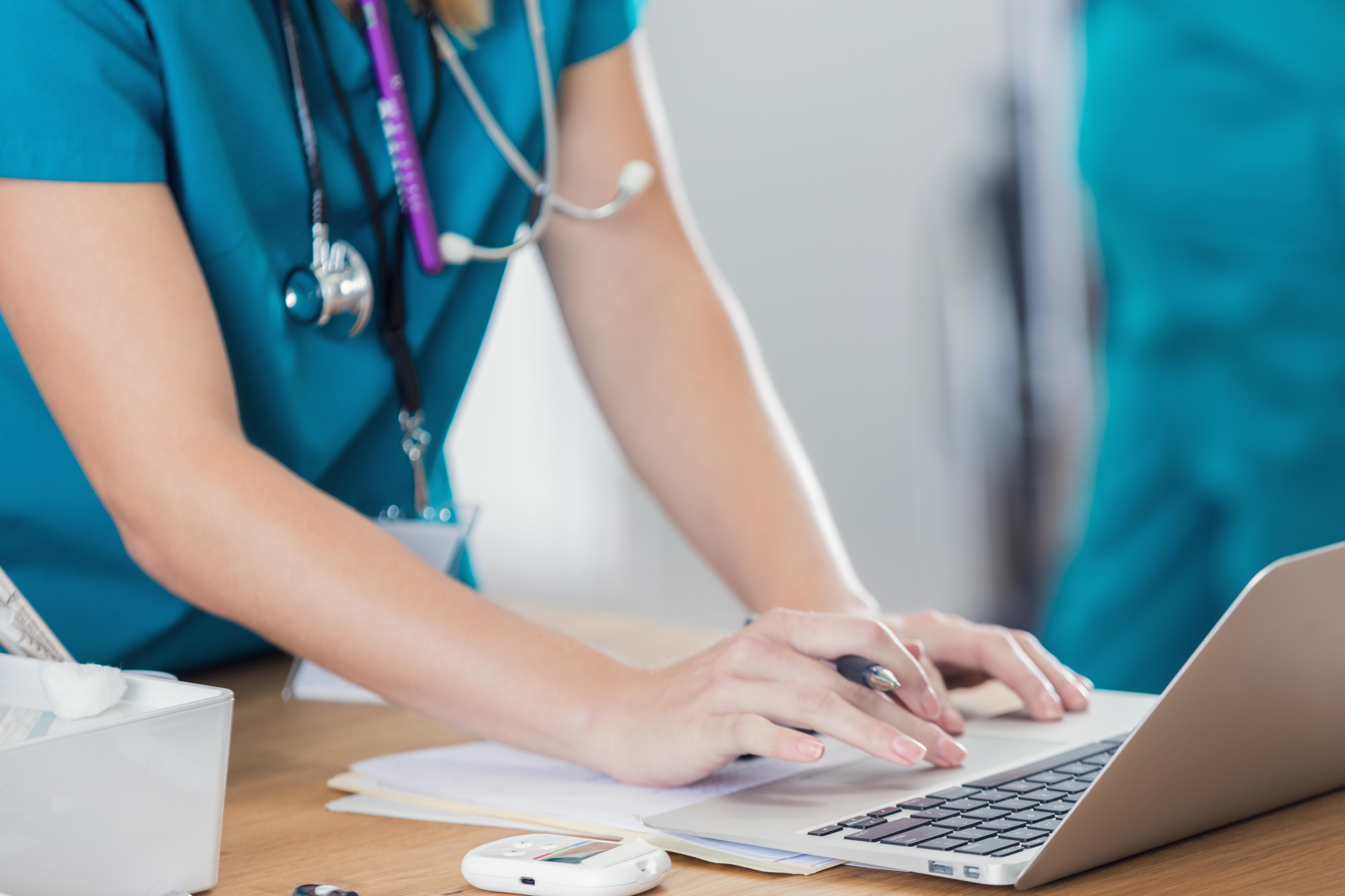 Closeup of a nurse working on a laptop