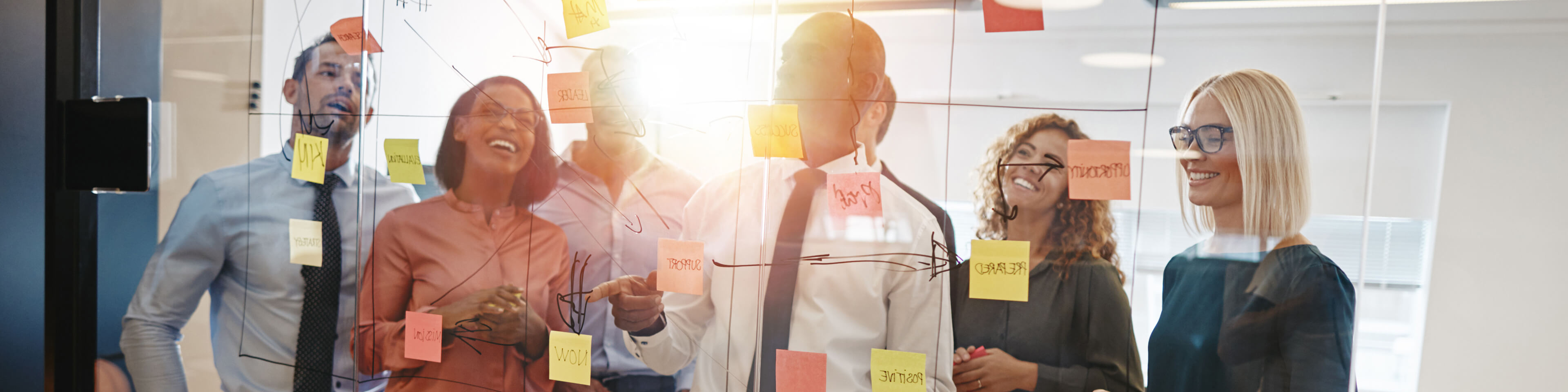 Group of men and women standing at a whiteboard, looking at a flowchart with sticky notes on it. the people are smiling.