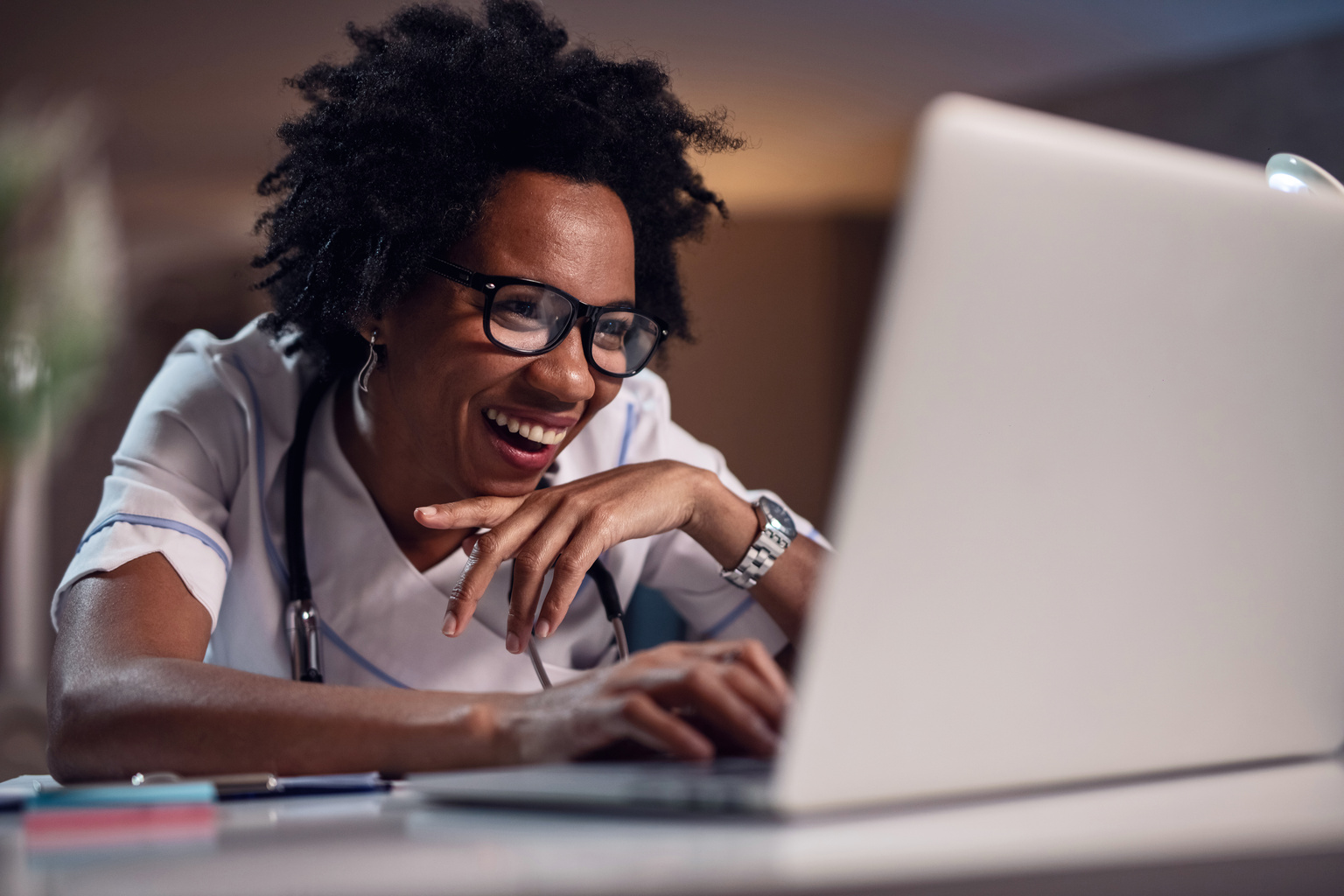 Happy black female doctor surfing the internet on laptop