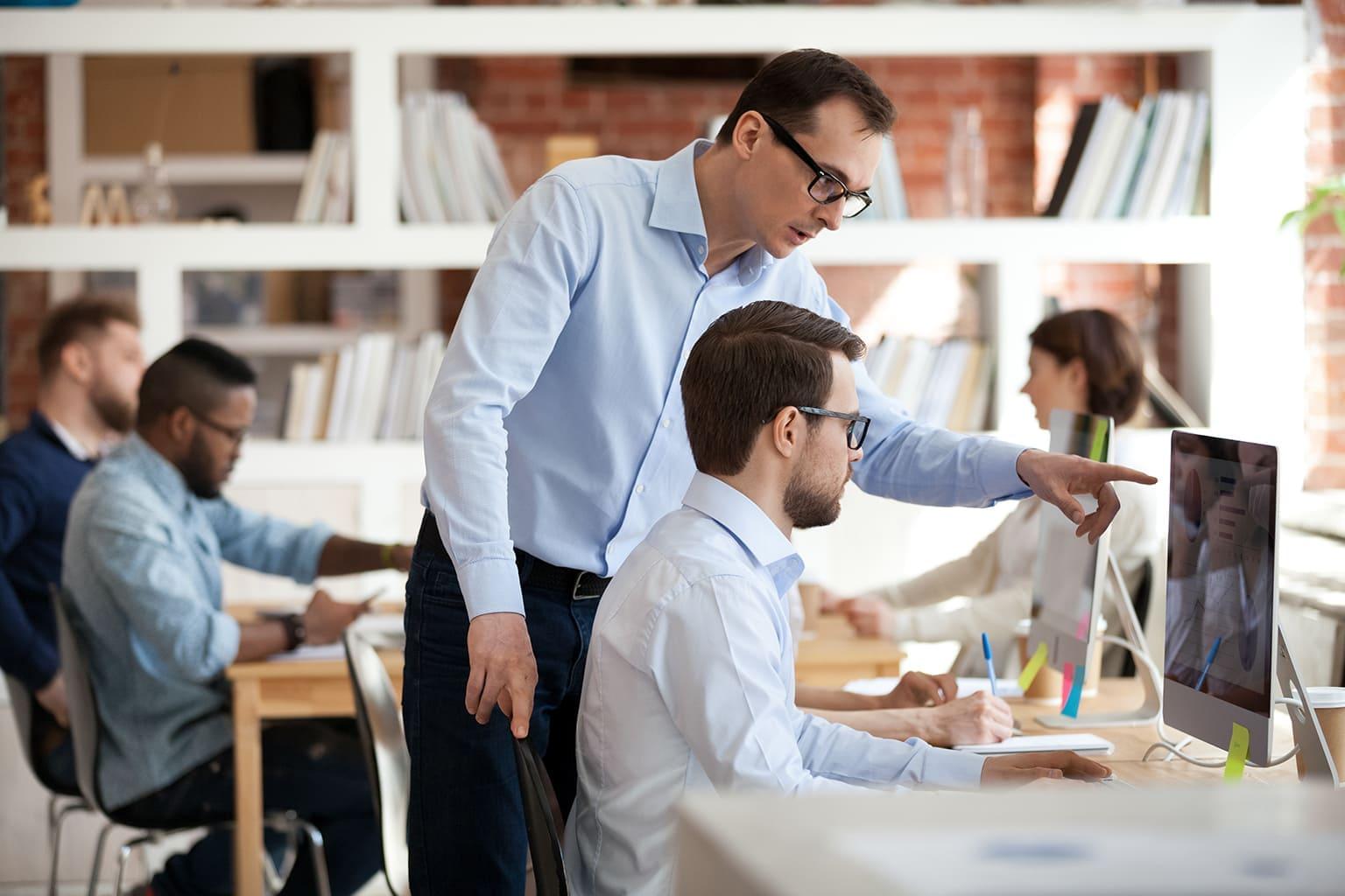 senior helpt junior boekhouder tijdens training boekhouden
