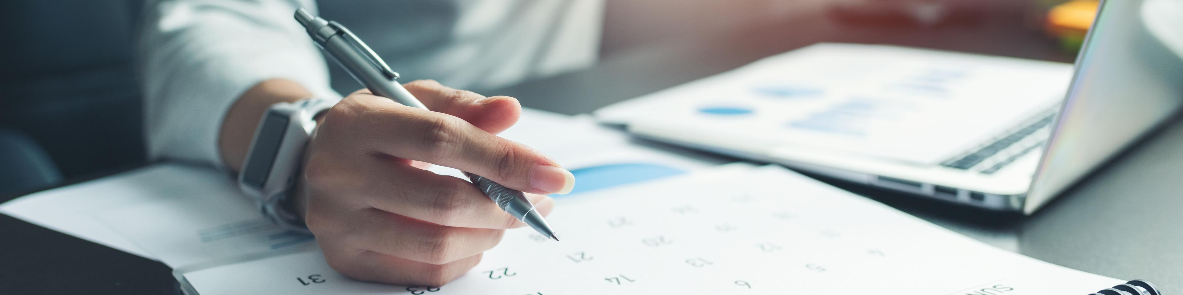 Holding a pen over a calendar