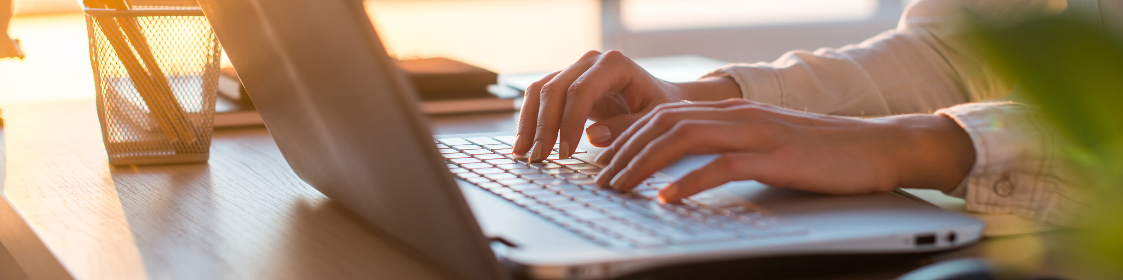 woman typing on a laptop - close-up of hands