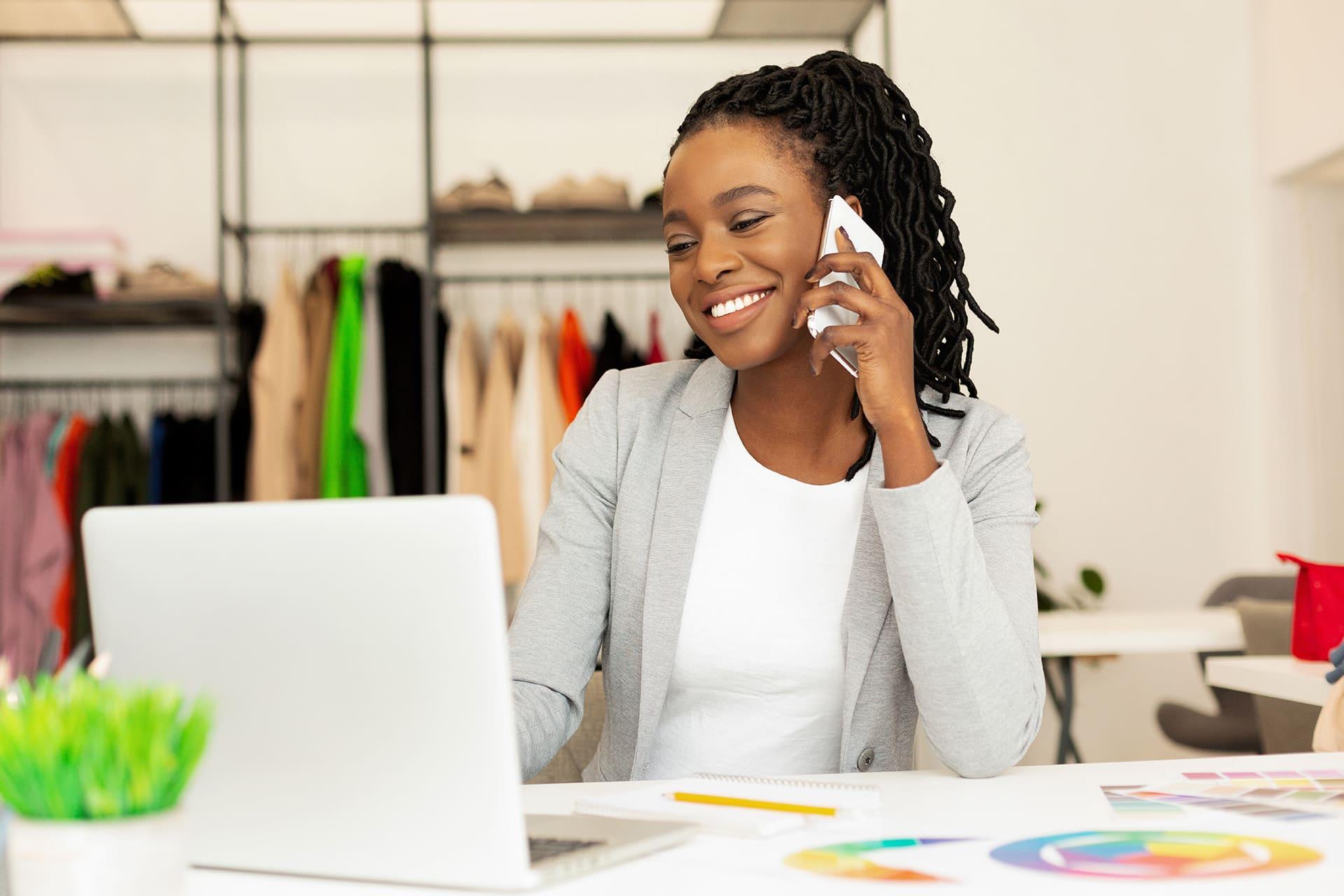 Vrouw met telefoon aan haar oor achter laptop