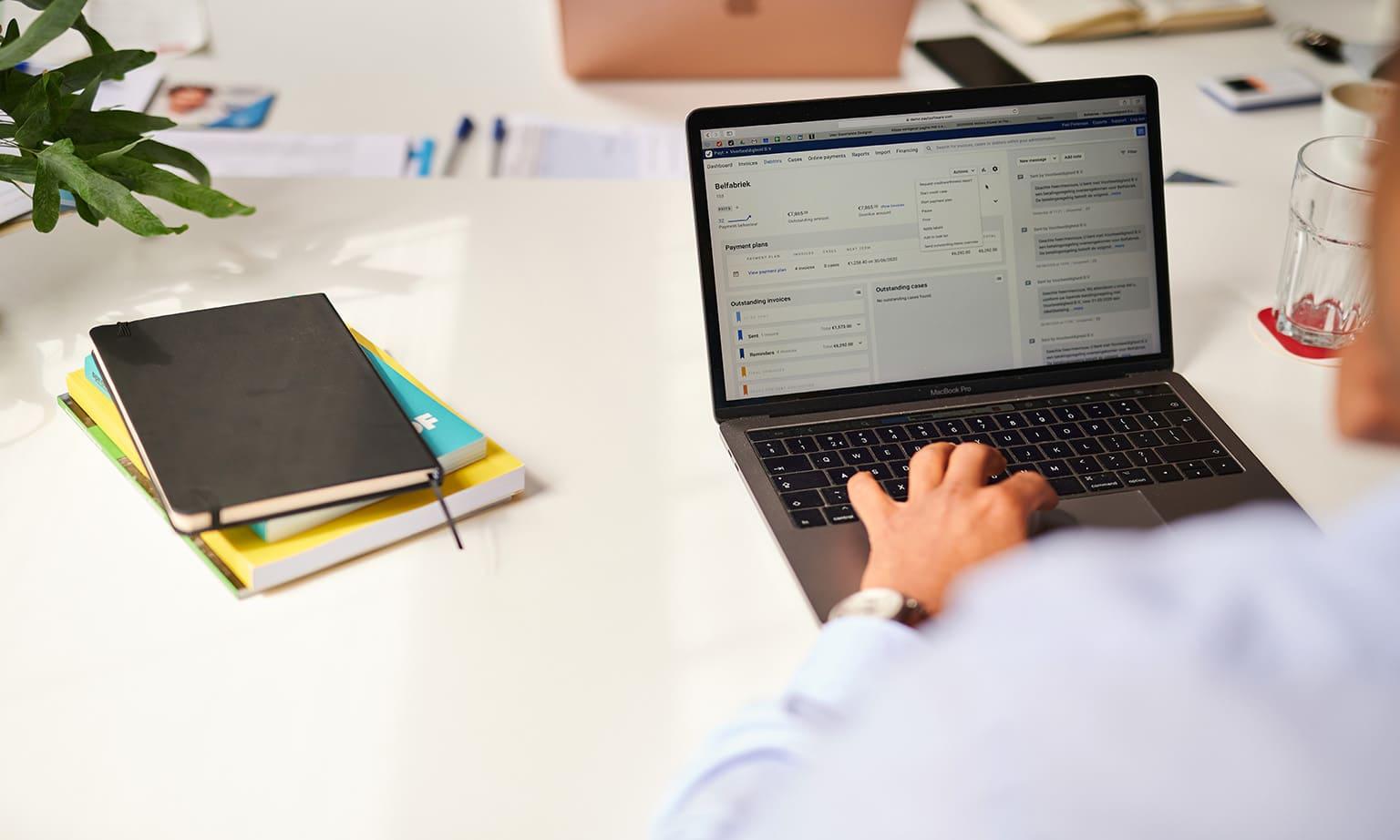 Man is bezig met debiteurenbeheer Payt op laptop