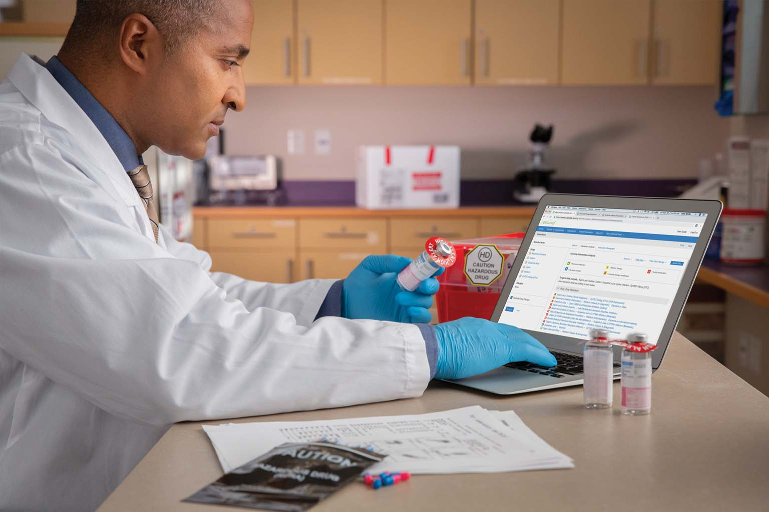 doctor holding vial near laptop displaying Lexicomp