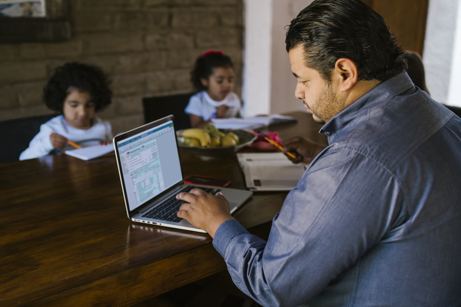 Man working from home surrounded by children