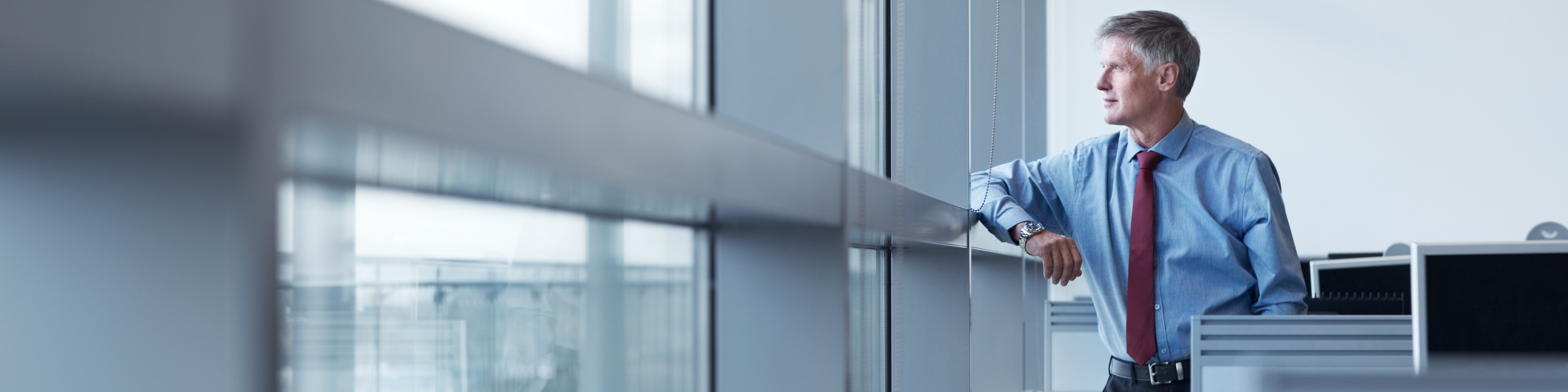 Shot of a mature businessman looking out the window of his office