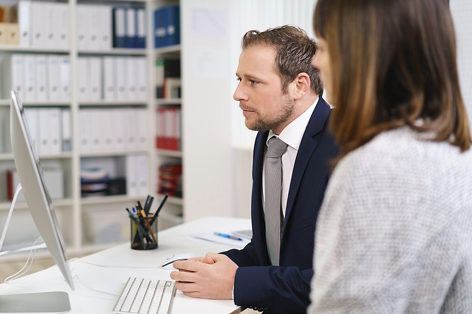 Man och kvinna vid dator tittar på Skatteinformation