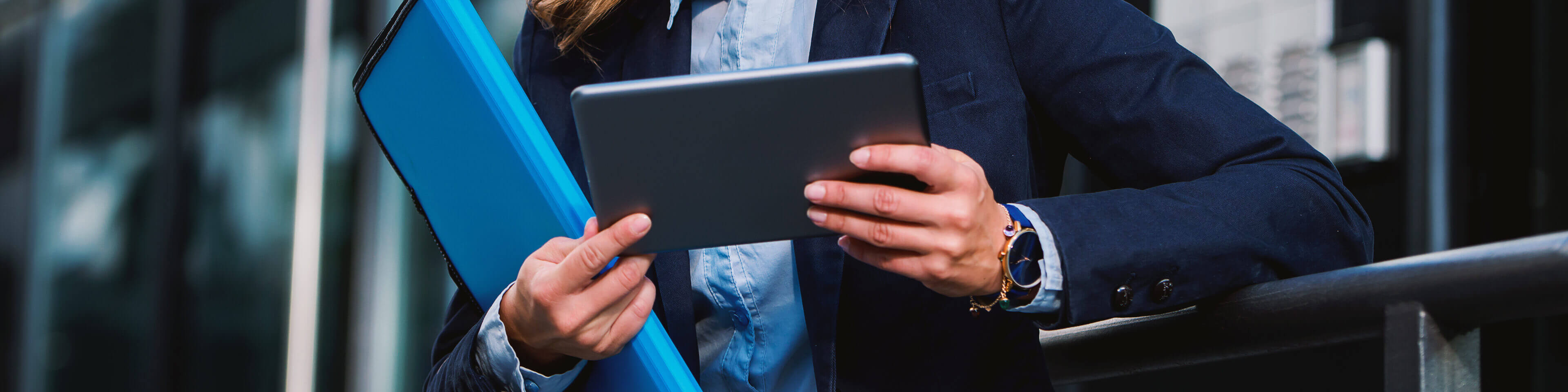 woman in business attire outside holding a tablet