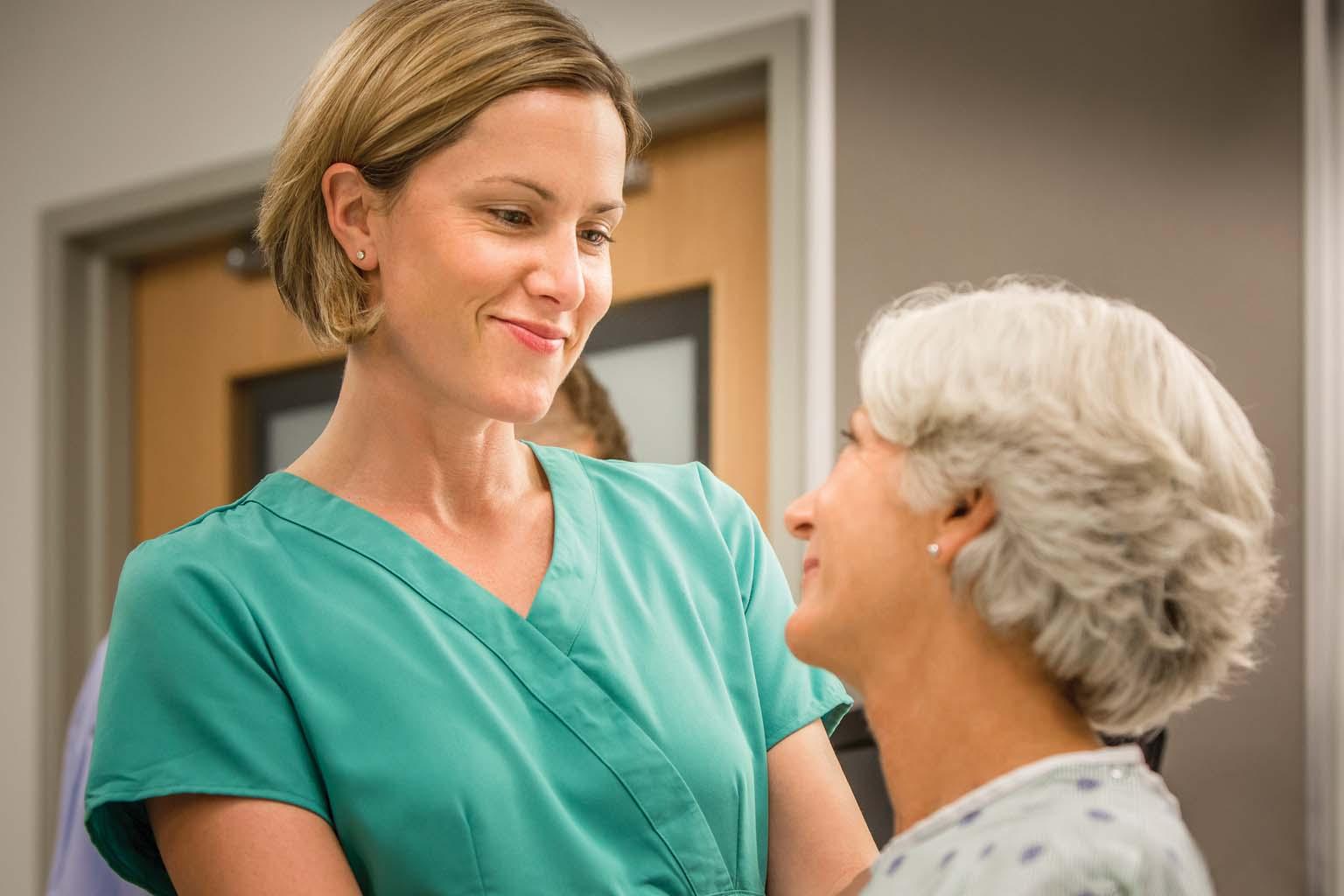 nurse comforting female patient in hospital