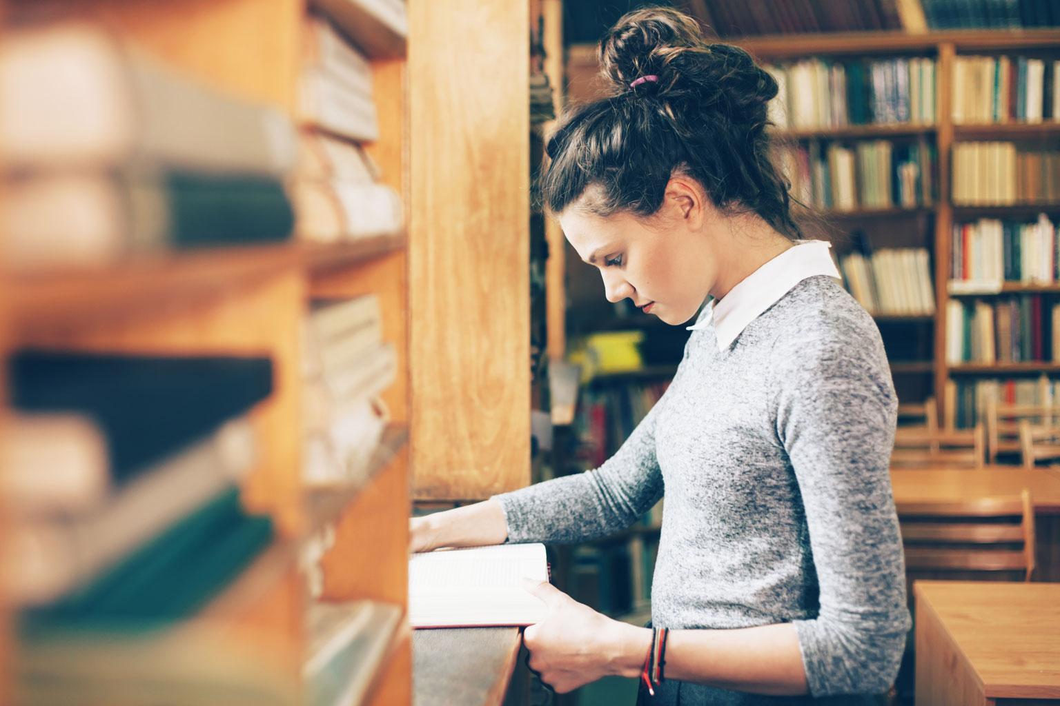 Studentka szkoły wyższej przegląda książkę w bibliotece