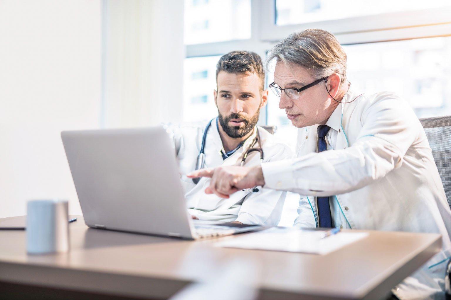 Dwóch lekarzy na komputerze sprawdza przepisy prawa medycznego