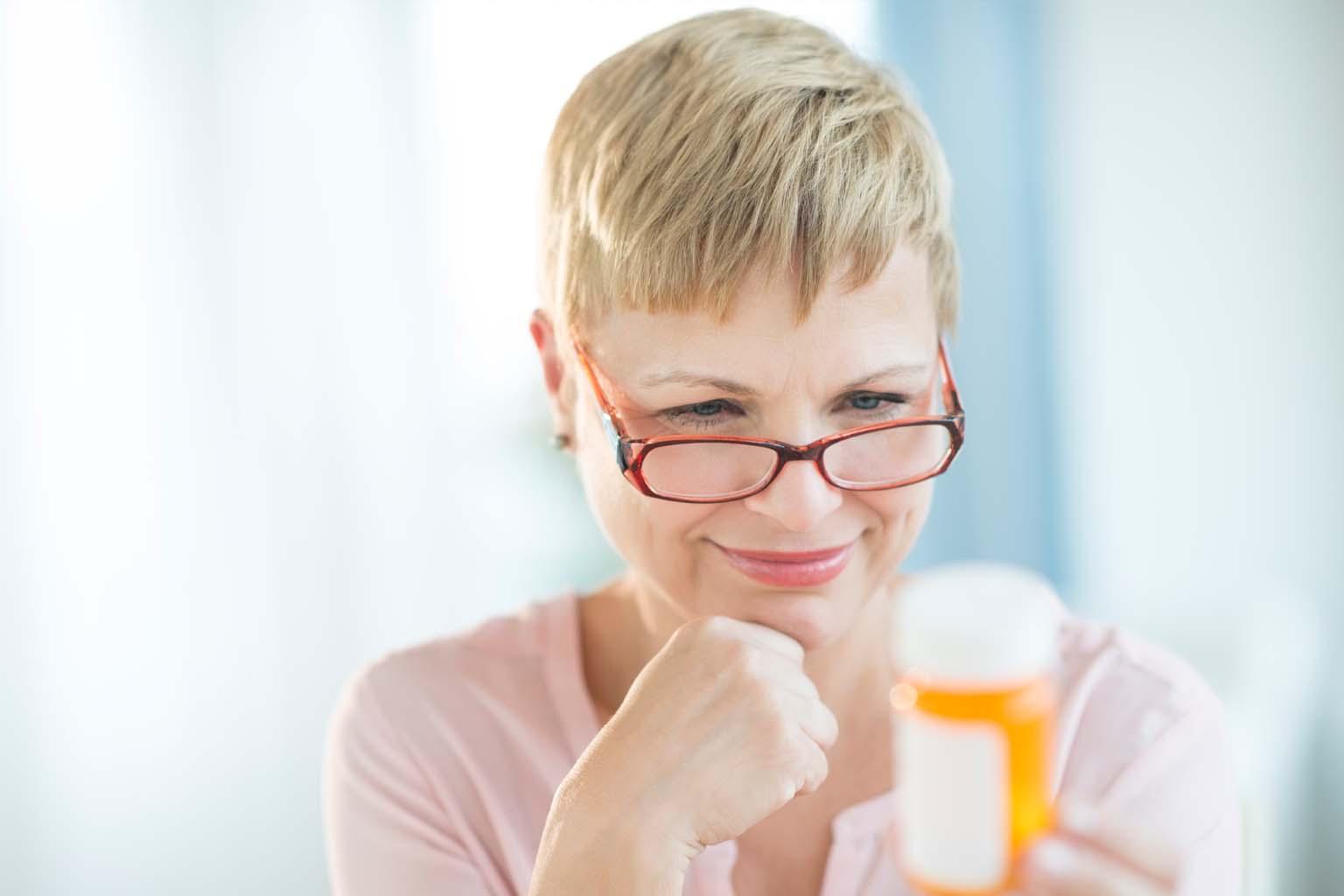 woman reading label on prescription bottle