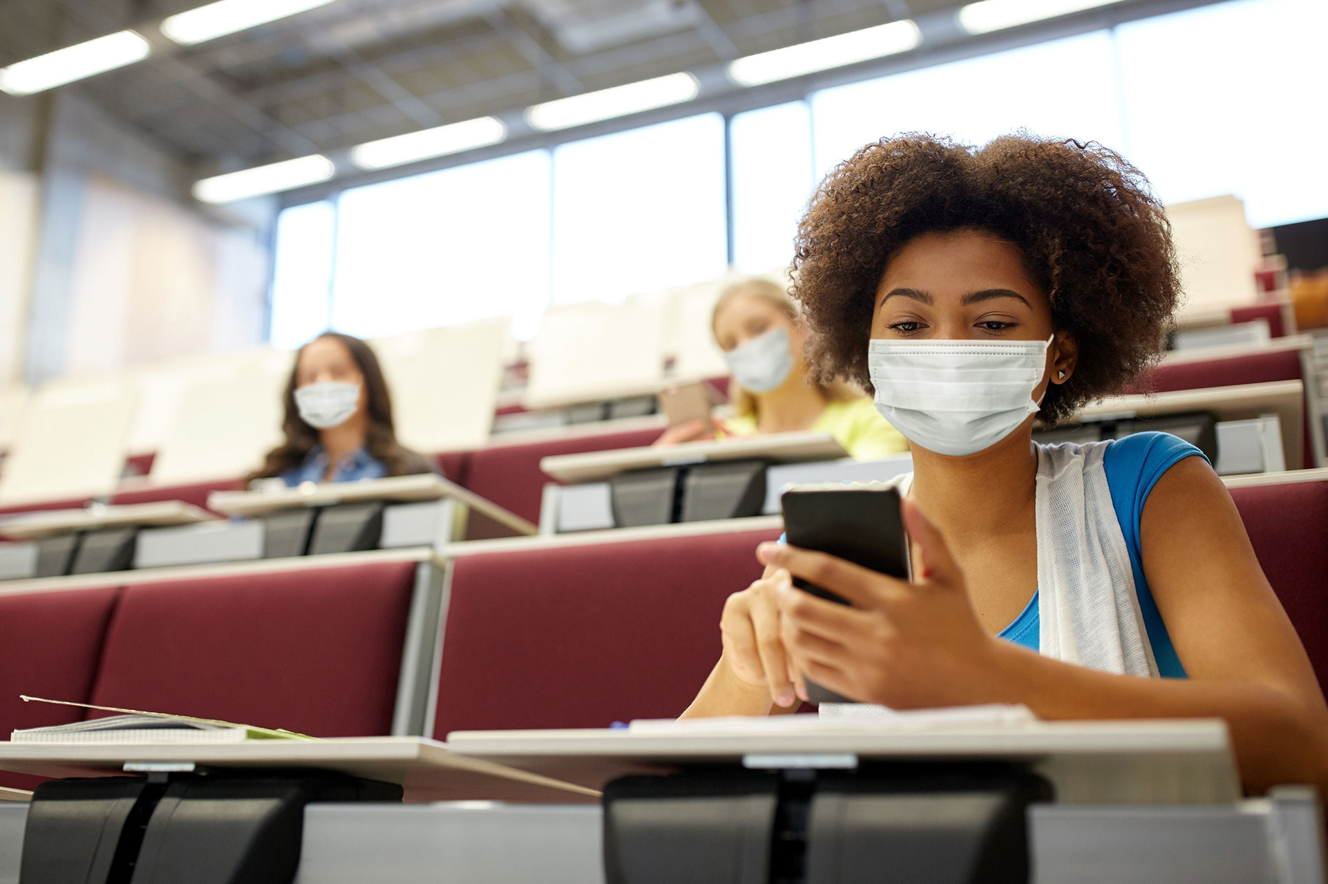 Black female student on her phone in a classroom