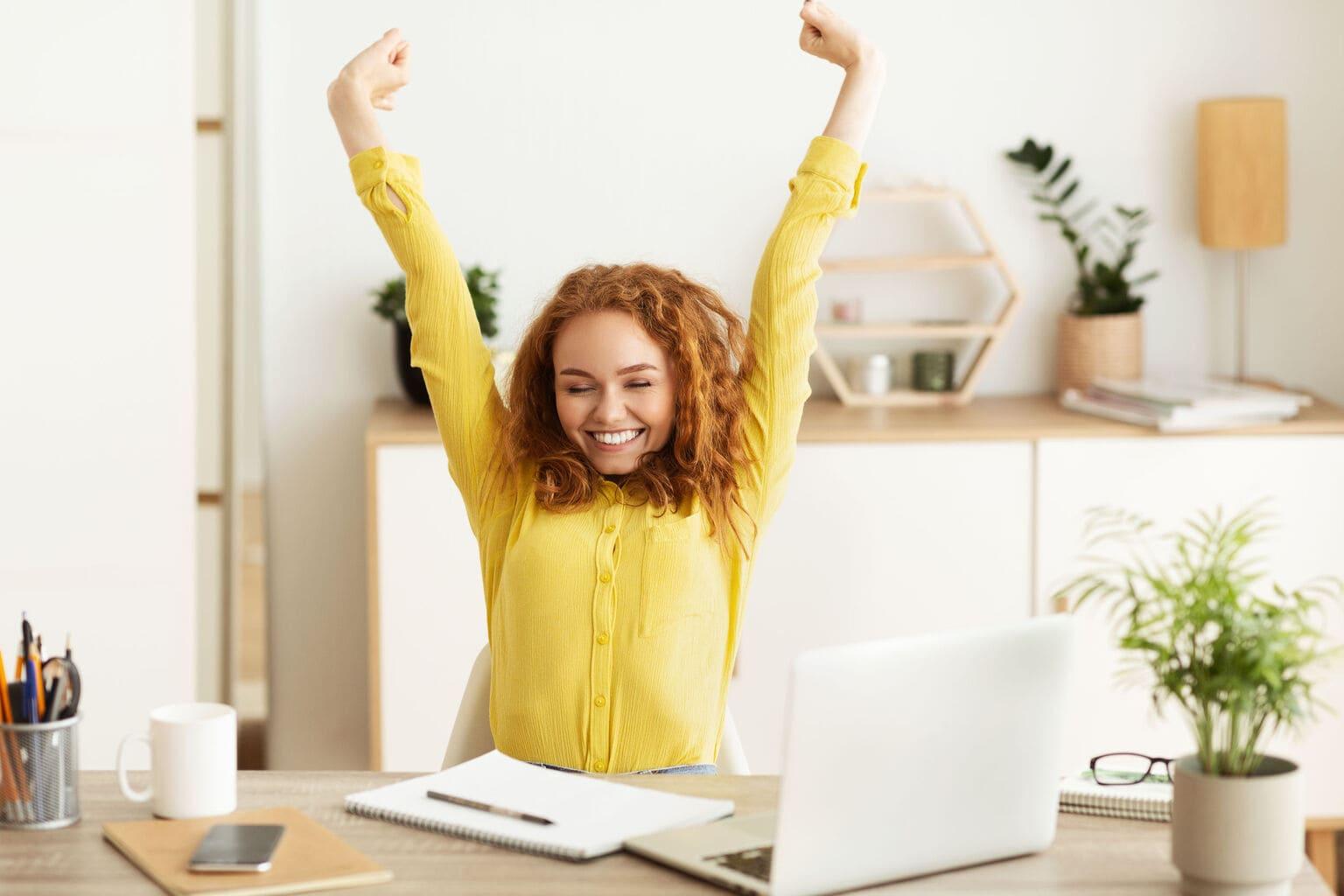 Vrouw met rood haar enthousiast achter laptop