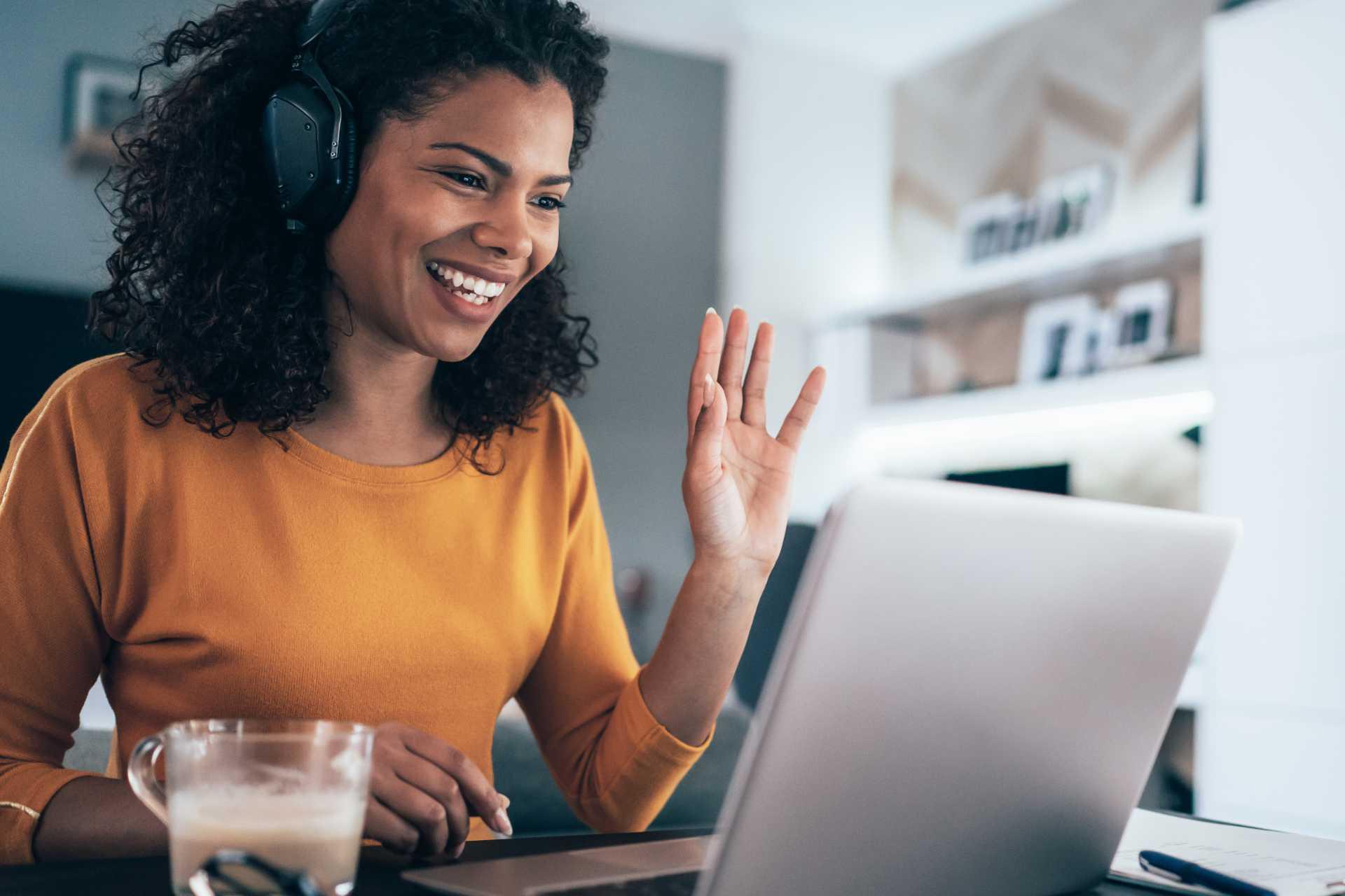 Woman waves at laptop