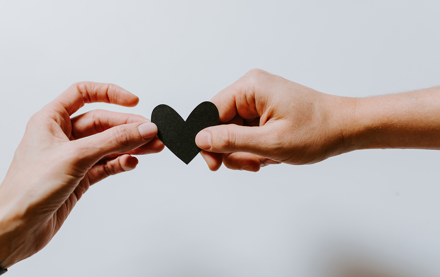 Two hands holding a black paper heart