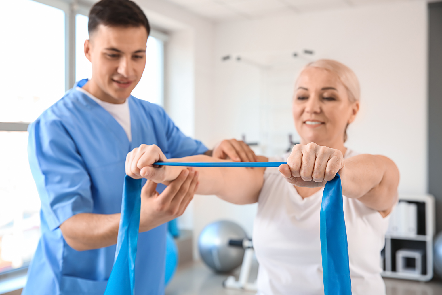 Physiotherapist helping patient with strengthening arms