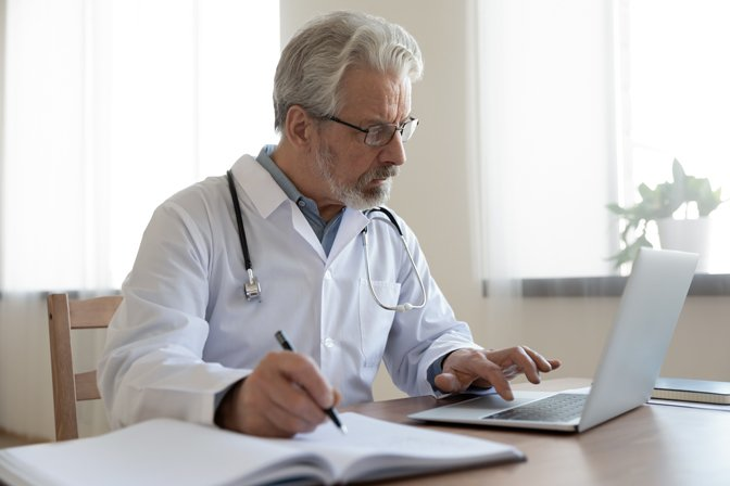 Doctor sitting at desk with laptop and notebook
