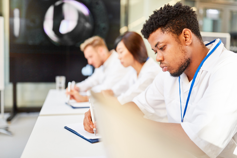 Young medicine students writing at desk