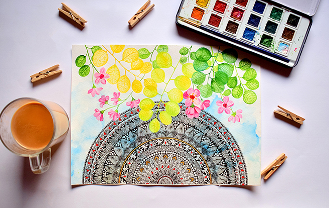 Mandala with watercolor leaves and flowers on paper with a mug of coffee and paint palette next to it