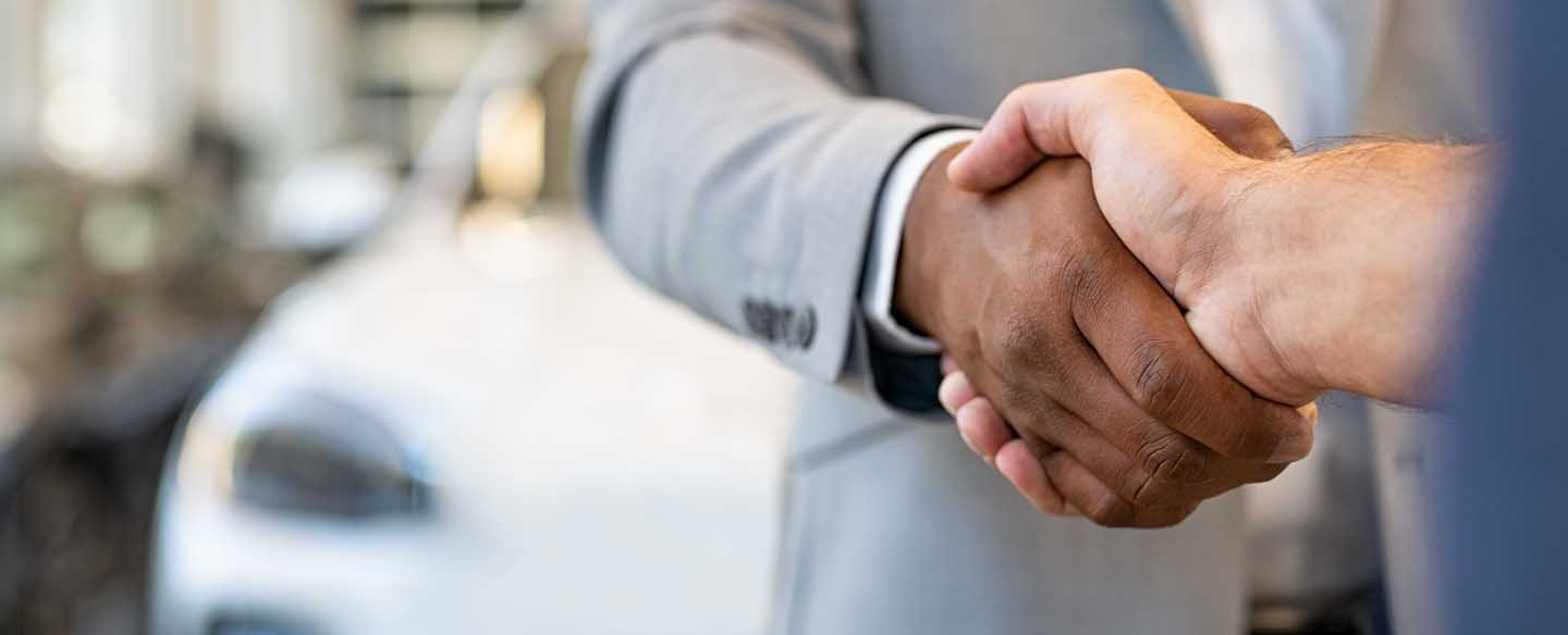 a person selling a car to someone else over a handshake